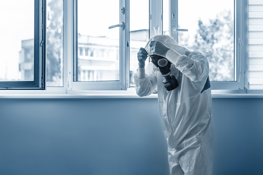 Man wearing protective biological suit and gas-mask due to mers coronavirus global pandemic warning and danger. Medic sphysician scientist make disinfection and ventilation at hospital clinic room