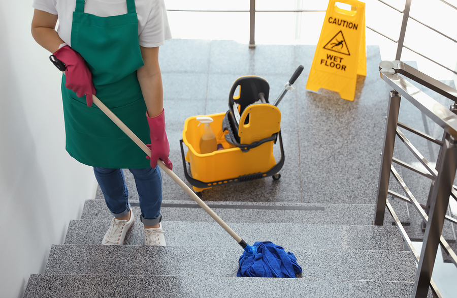 Young woman with mop cleaning stairs indoors